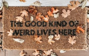front door mat with fall leaves scattered around it, with text that says the good kind of weird lives here